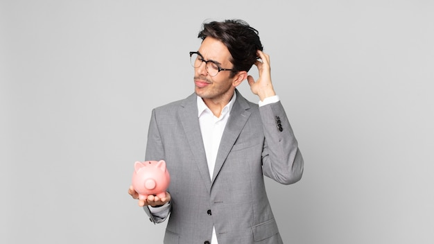 Młody latynoski mężczyzna czuje się zakłopotany i zdezorientowany, drapiąc się po głowie i trzymając świnka skarbonka