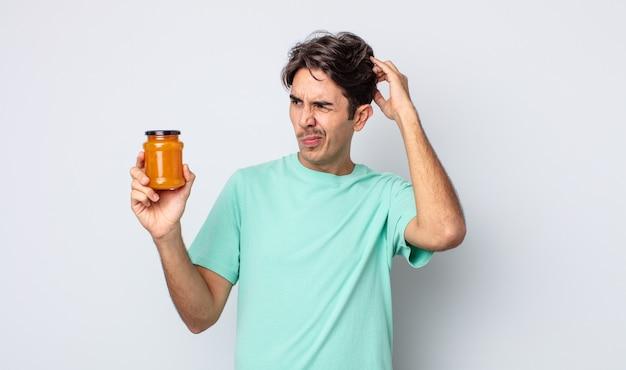 Młody latynoski mężczyzna czuje się zakłopotany i zdezorientowany, drapiąc się po głowie. koncepcja galaretki brzoskwiniowej