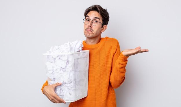 Młody latynoski mężczyzna czuje się zakłopotany, zdezorientowany i wątpi. koncepcja śmieci z kulkami papierowymi