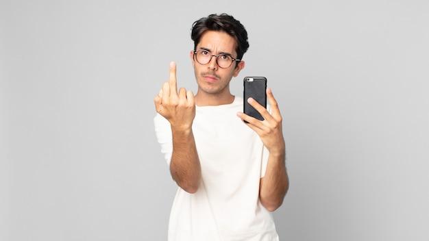 Młody latynoski mężczyzna czuje się zły, zirytowany, buntowniczy i agresywny i trzyma smartfon