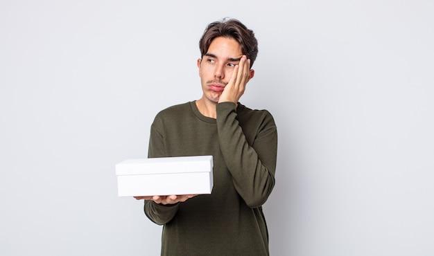 Młody latynoski mężczyzna czuje się znudzony, sfrustrowany i senny po męczącym dniu. koncepcja białego pudełka
