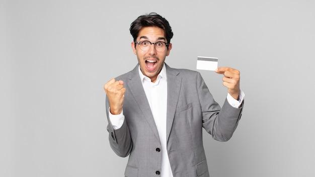 Młody latynoski mężczyzna czuje się zszokowany, śmieje się i świętuje sukces i trzyma kartę kredytową