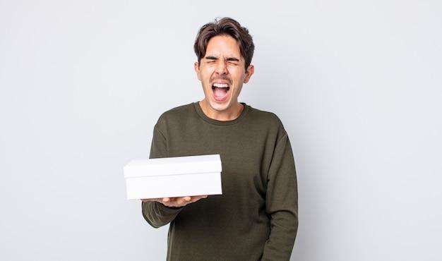 Młody latynoski mężczyzna krzyczy agresywnie, wygląda na bardzo rozgniewanego. koncepcja białego pudełka