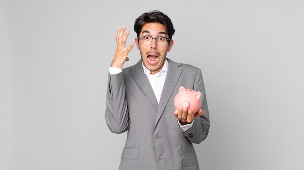 Młody latynoski mężczyzna krzyczy z rękami w górze i trzyma skarbonkę