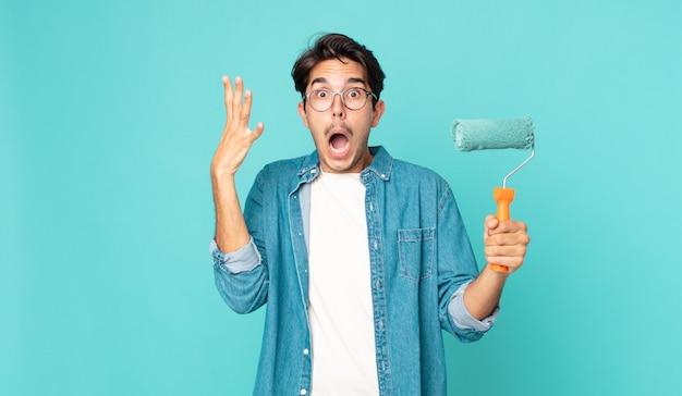 Młody latynoski mężczyzna krzyczy z rękami w górze i trzyma wałek do malowania