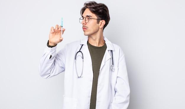 Młody latynoski mężczyzna myślący, wyobrażający sobie lub marzący o widoku profilu. koncepcja strzykawki lekarza