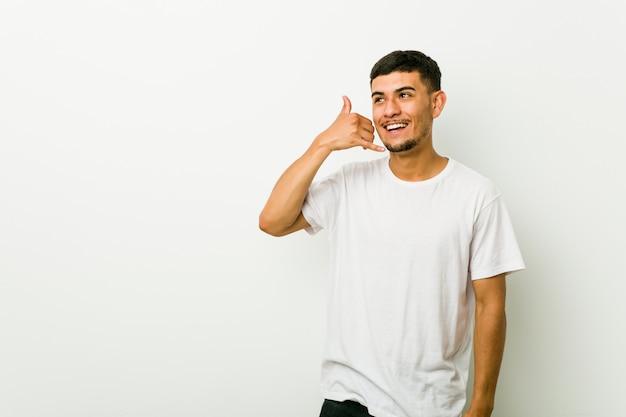Młody latynoski mężczyzna pokazuje telefonu komórkowego wezwania gest z palcami.