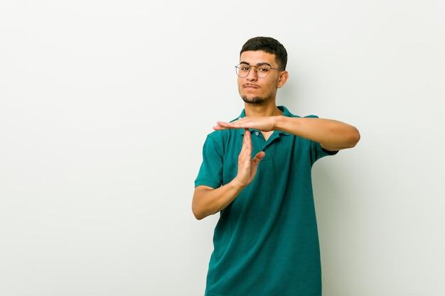 Młody latynoski mężczyzna pokazuje timeout gest.