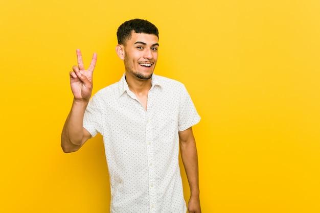 Młody latynoski mężczyzna pokazuje zwycięstwo znaka i uśmiecha się szeroko.