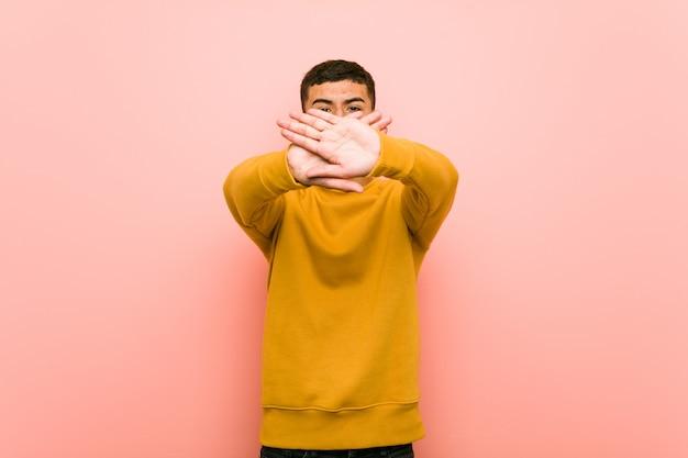 Młody latynoski mężczyzna robi zaprzeczeniu gestowi