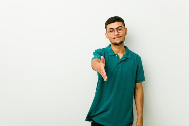 Młody latynoski mężczyzna rozciągania ręka przy kamerą w powitanie gescie.