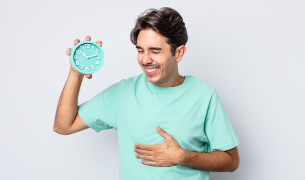 Młody latynoski mężczyzna śmiejący się głośno z jakiegoś przezabawnego żartu. koncepcja budzika