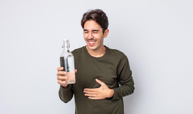 Młody latynoski mężczyzna śmiejący się głośno z jakiegoś przezabawnego żartu. koncepcja butelki z wodą