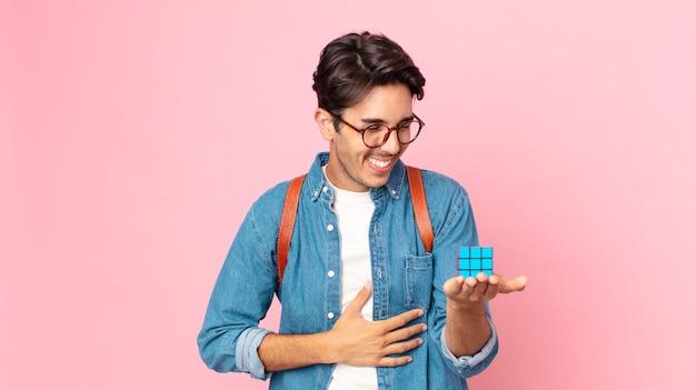 Młody latynoski mężczyzna śmiejący się głośno z jakiegoś przezabawnego żartu z grą na inteligencję