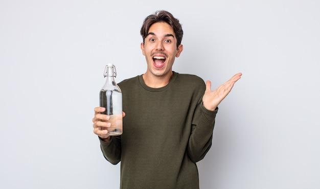 Młody, latynoski mężczyzna, szczęśliwy i zdumiony czymś niewiarygodnym. koncepcja butelki z wodą