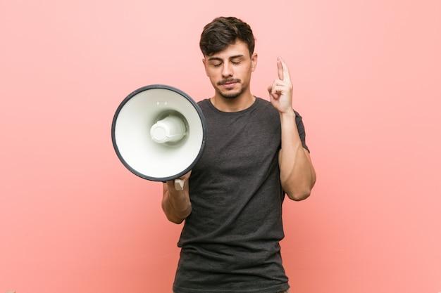 Młody latynoski mężczyzna trzyma megafon krzyżuje palce dla mieć szczęście