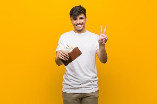 Młody latynoski mężczyzna trzyma portfel pokazuje numer dwa z palcami.