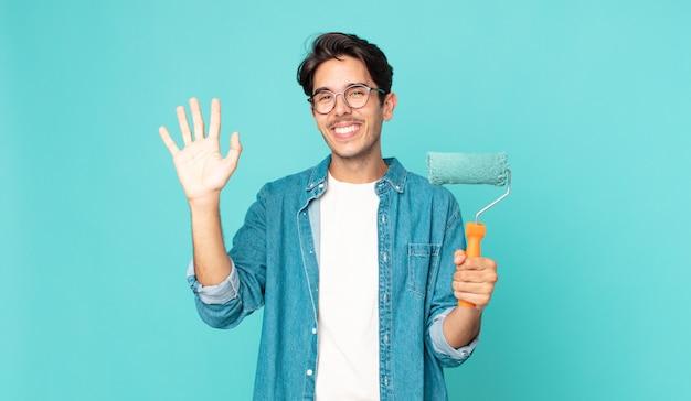 Młody latynoski mężczyzna uśmiecha się radośnie, macha ręką, wita cię i wita i trzyma wałek do malowania