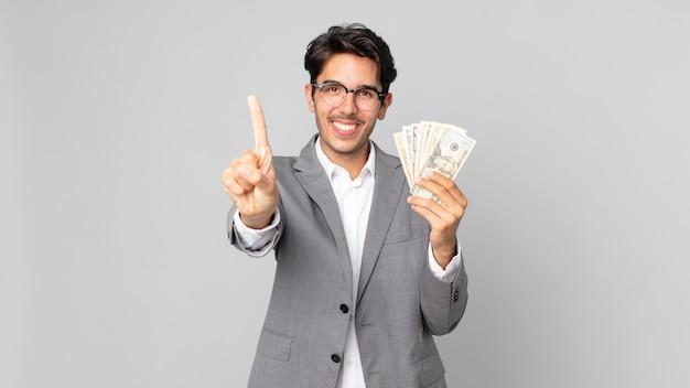 Młody latynoski mężczyzna uśmiechający się dumnie i pewnie robiąc numer jeden