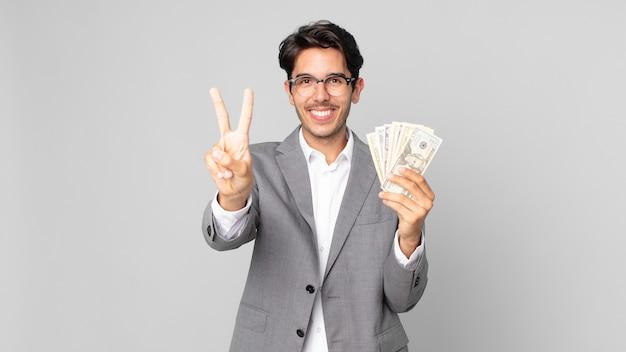 Młody latynoski mężczyzna uśmiechający się i wyglądający przyjaźnie, pokazując numer dwa