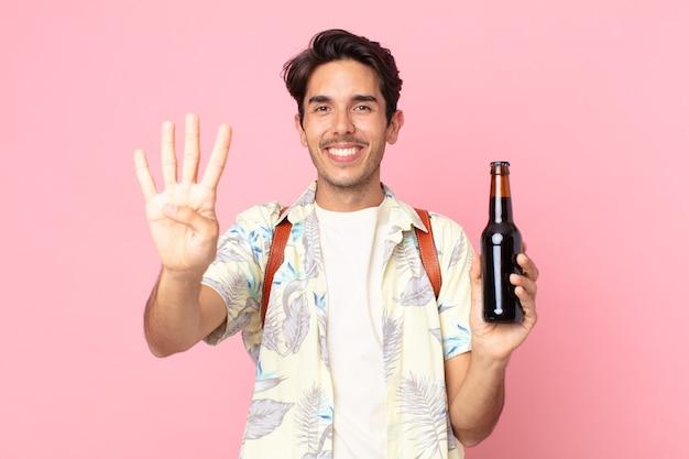 Młody latynoski mężczyzna uśmiechający się i wyglądający przyjaźnie, pokazujący numer cztery i trzymający butelkę piwa