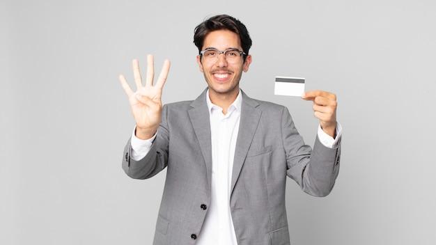 Młody latynoski mężczyzna uśmiechający się i wyglądający przyjaźnie, pokazujący numer cztery i trzymający kartę kredytową