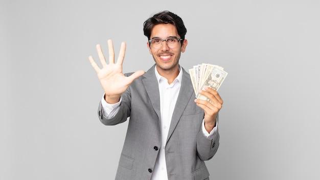 Młody latynoski mężczyzna uśmiechający się i wyglądający przyjaźnie, pokazujący numer pięć