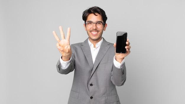 Młody latynoski mężczyzna uśmiechający się i wyglądający przyjaźnie, pokazujący numer trzy i trzymający smartfona
