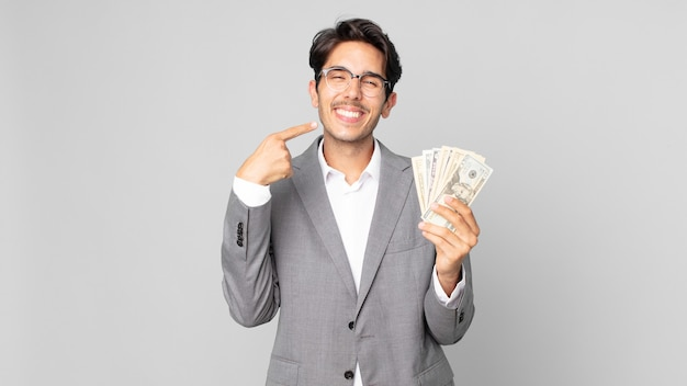 Młody latynoski mężczyzna uśmiechający się pewnie, wskazując na swój szeroki uśmiech