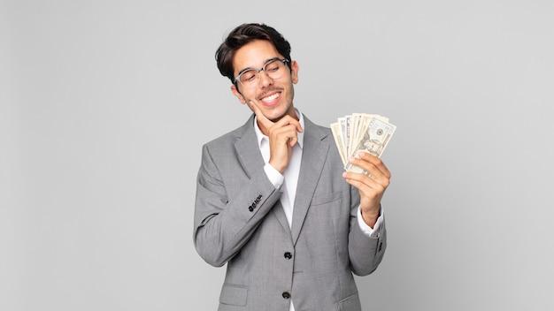 Młody latynoski mężczyzna uśmiechający się radośnie i marzący lub wątpiący