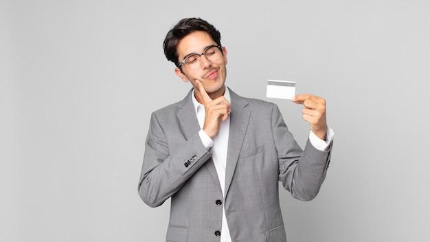 Młody latynoski mężczyzna uśmiechający się radośnie i marzący na jawie lub wątpiący i trzymający kartę kredytową
