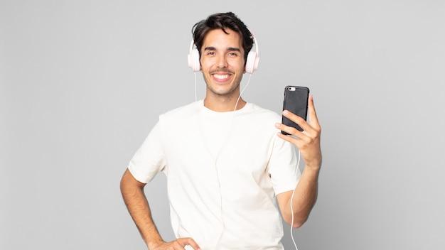 Młody latynoski mężczyzna uśmiechający się radośnie z ręką na biodrze i pewny siebie ze słuchawkami i smartfonem