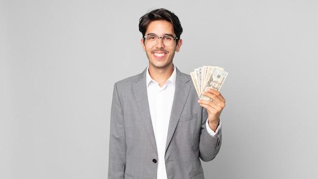Młody latynoski mężczyzna uśmiechający się radośnie z ręką na biodrze i pewny siebie