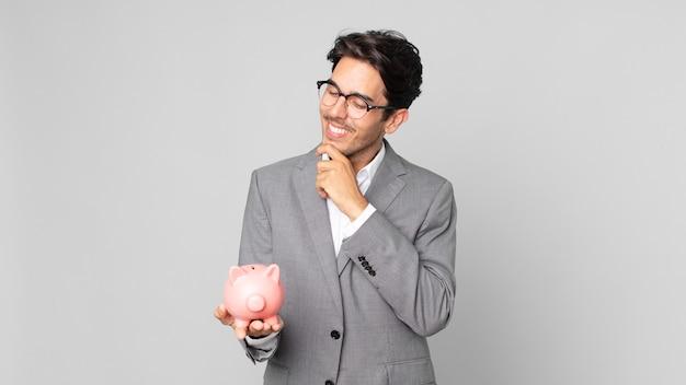 Młody latynoski mężczyzna uśmiechający się ze szczęśliwym, pewnym siebie wyrazem twarzy z ręką na brodzie i trzymający skarbonkę