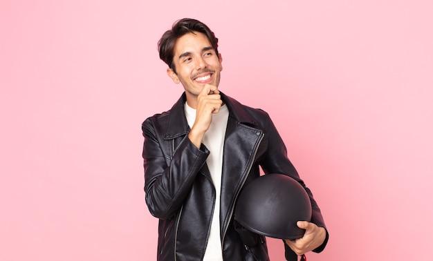 Młody latynoski mężczyzna uśmiechający się ze szczęśliwym, pewnym siebie wyrazem twarzy z ręką na brodzie. koncepcja motocyklisty