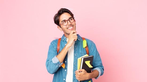 Młody latynoski mężczyzna uśmiechający się ze szczęśliwym, pewnym siebie wyrazem twarzy z ręką na brodzie. koncepcja studenta