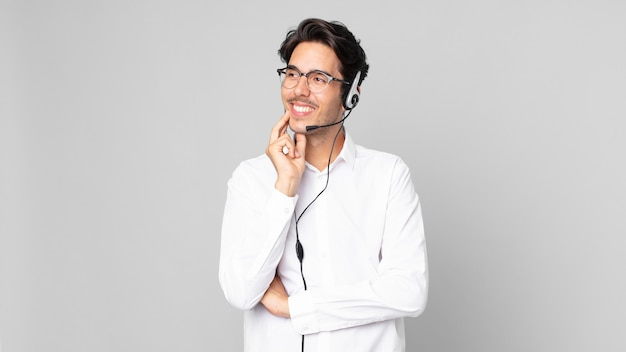 Młody latynoski mężczyzna uśmiechający się ze szczęśliwym, pewnym siebie wyrazem twarzy z ręką na brodzie. koncepcja telemarketera