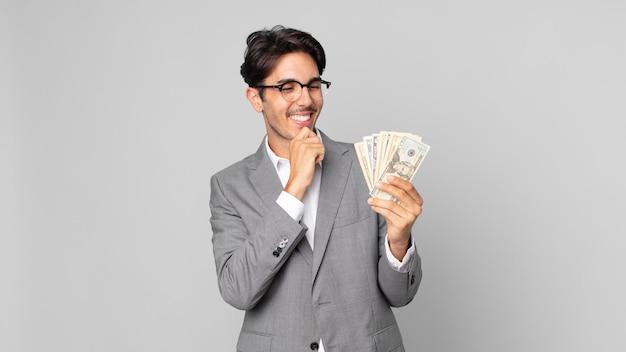 Młody latynoski mężczyzna uśmiechający się ze szczęśliwym, pewnym siebie wyrazem twarzy z ręką na brodzie