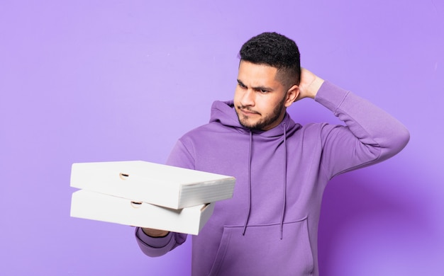 Młody latynoski mężczyzna wątpiący lub niepewny wyraz twarzy i trzymający pizze na wynos
