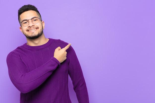 Młody latynoski mężczyzna wskazujący lub pokazujący