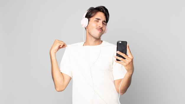 Młody latynoski mężczyzna wyglądający arogancko, odnoszący sukcesy, pozytywnie nastawiony i dumny ze słuchawkami i smartfonem