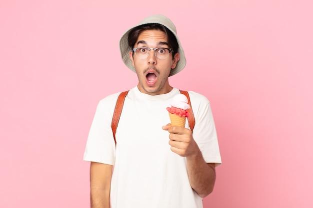 Młody latynoski mężczyzna wyglądający na bardzo zszokowanego lub zdziwionego i trzymający lody