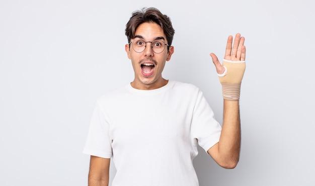 Młody latynoski mężczyzna wyglądający na bardzo zszokowanego lub zdziwionego. koncepcja bandaża ręcznego