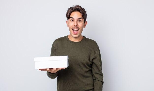 Młody latynoski mężczyzna wyglądający na bardzo zszokowanego lub zdziwionego. koncepcja białego pudełka