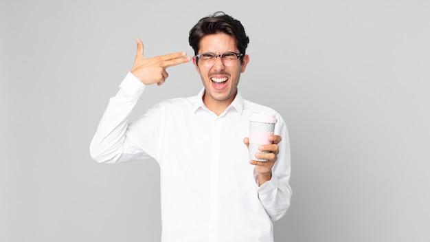 Młody latynoski mężczyzna wyglądający na nieszczęśliwego i zestresowanego, samobójczy gest robiący znak pistoletu i trzymający kawę na wynos