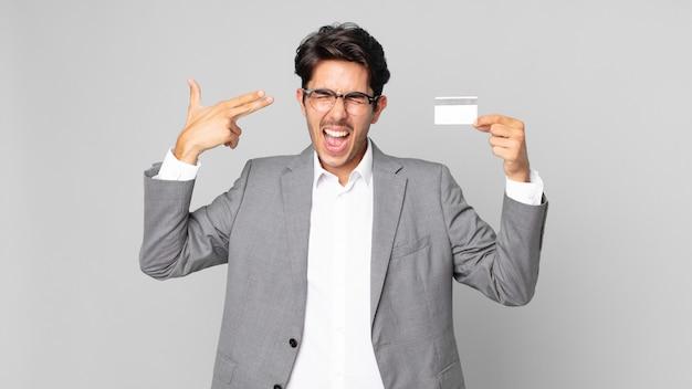 Młody latynoski mężczyzna wyglądający na niezadowolonego i zestresowanego, samobójczy gest, robiący znak pistoletu i trzymający kartę kredytową