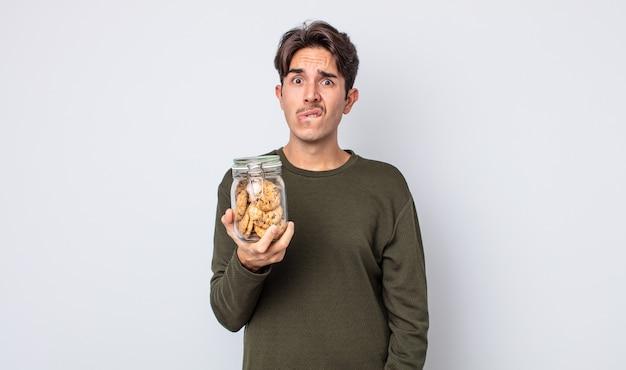 Młody latynoski mężczyzna wyglądający na zdziwionego i zdezorientowanego. koncepcja ciasteczek