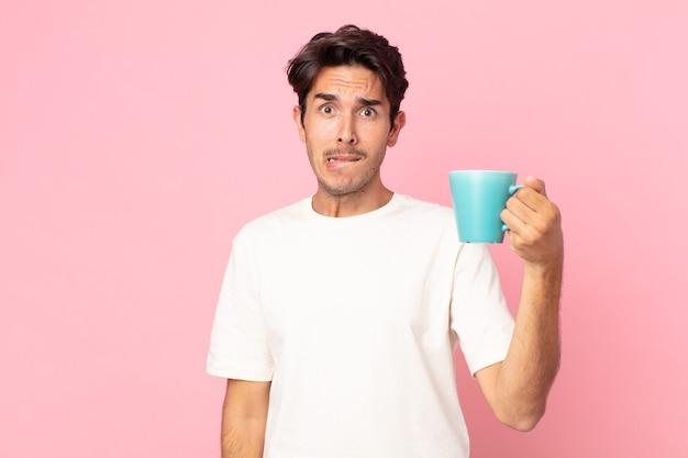 Młody latynoski mężczyzna wyglądający na zdziwionego i zdezorientowanego, trzymający kubek z kawą