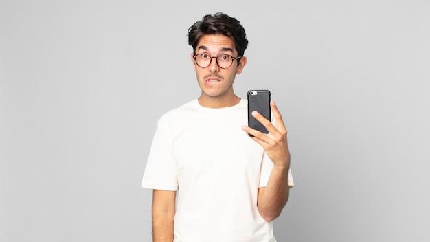 Młody latynoski mężczyzna wyglądający na zdziwionego i zdezorientowanego, trzymający smartfona