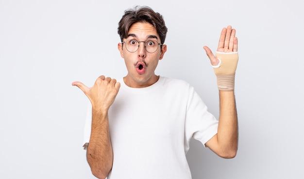 Młody latynoski mężczyzna wyglądający na zdziwionego z niedowierzaniem. koncepcja bandaża ręcznego